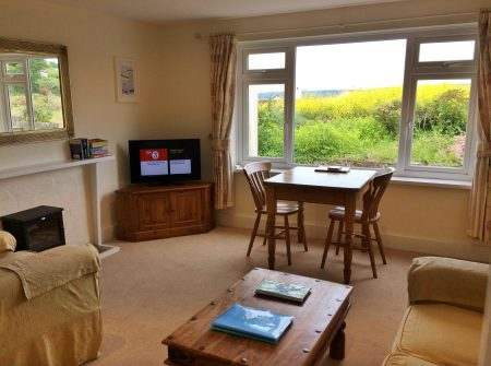 Lounge and dining area if Flat 9 Trevarthian House, Marazion. With views across the field and to the sea.